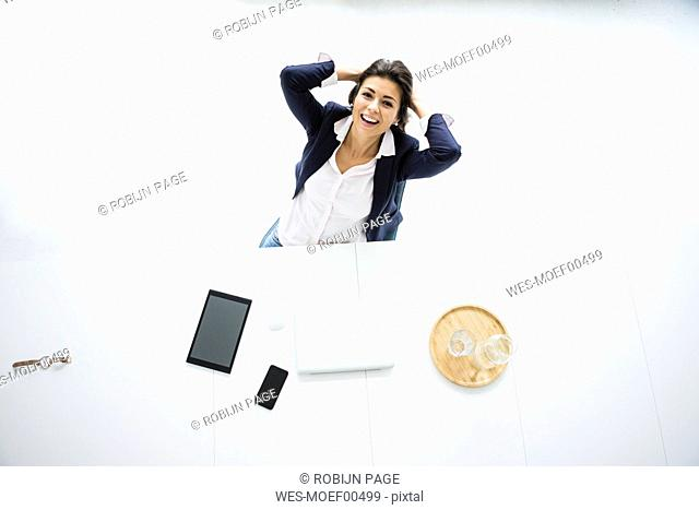 Portrait of laughing businesswoman having a break at desk in the office, top view