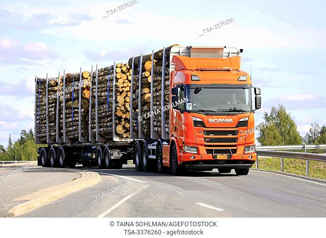 Turku, Finland. August 24, 2019. Orange Scania R730 XT truck pulls birch log load on timber trailer on highway ramp. Scania in Finland 70 years tour