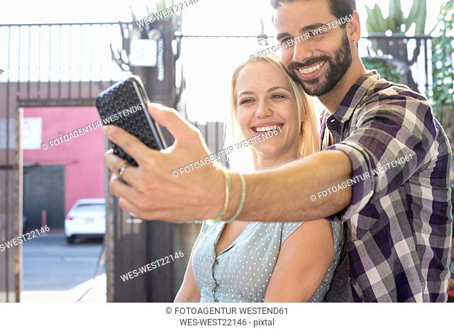 Happy young man with girlfriend taking a selfie