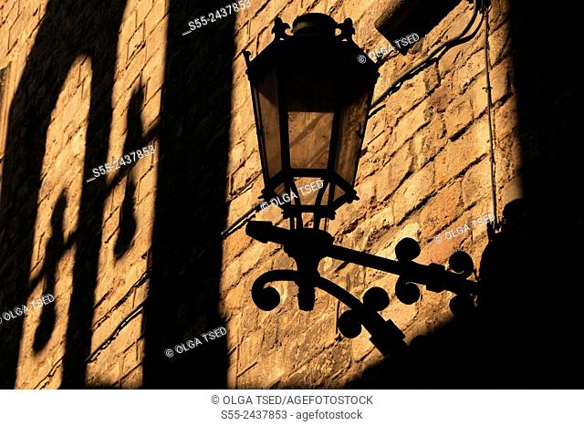 View of a streetlight and a bell tower reflection in Gothic quarter, Barcelona, Catalonia, Spain