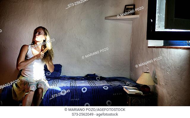 Woman sitting on bed brushing long blonde hair