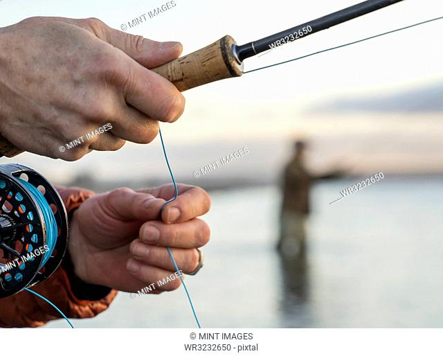 A closeup of a fly fisherman's hands holding his fly rod and line while fishing
