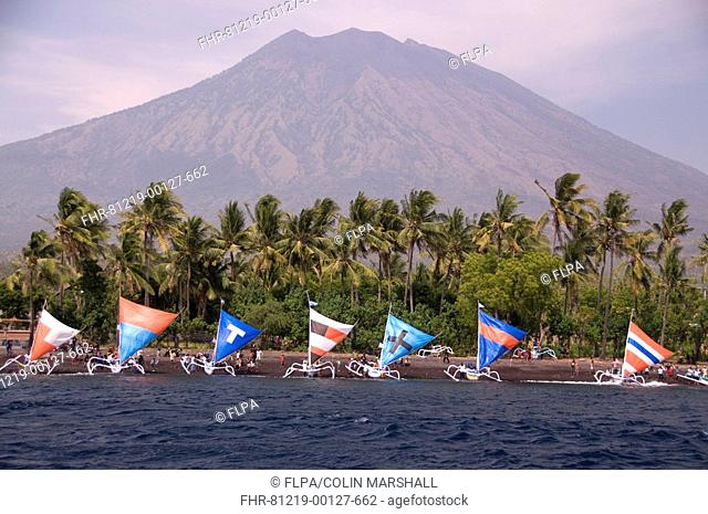 Boats with colourful sails prior to Jukung Race, with volcano in background, Mount Agung, Tulamben, Bali, Lesser Sunda Islands, Indonesia