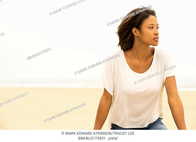 Pensive African American woman sitting at beach