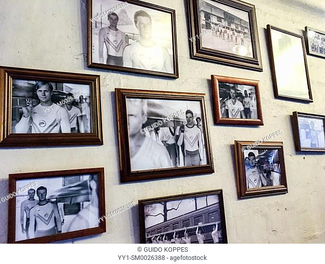Tilburg, Netherlands. Collection of Photographs and Photo Frames showing sports men on an interior cafe wall as interior decoration