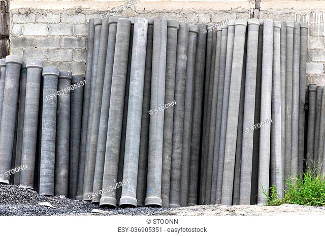 Stack of many concrete drainage pipe on wall in construction site