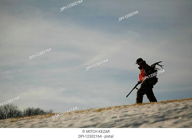 Hunter Walking Across While Hunting For Whitetail Deer
