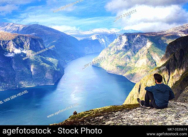 Man sitting on cliff edge alone enjoying aerial view backpacking lifestyle travel adventure outdoor summer vacations in Norway top of beautiful mountain blue...