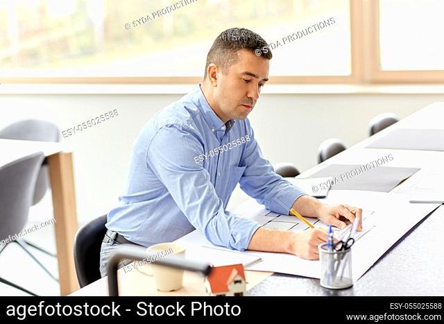 architect with blueprint working at home office
