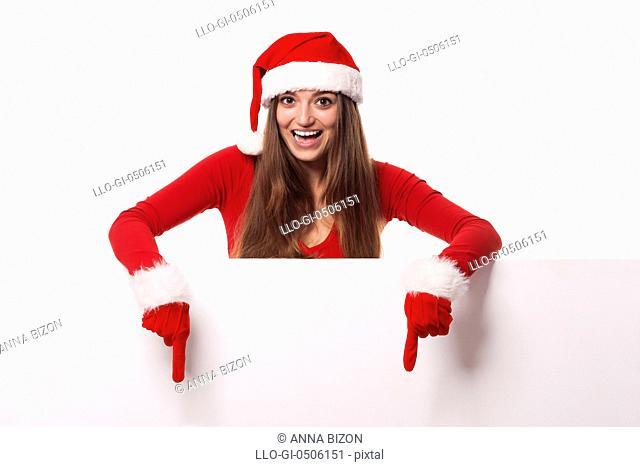 Excited woman wearing Santa hat showing on blank billboard, Debica, Poland