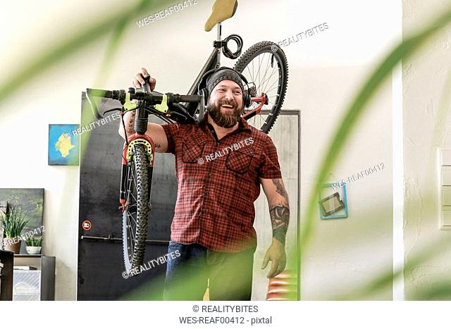 Laughing man wearing headphones carrying bicycle in office