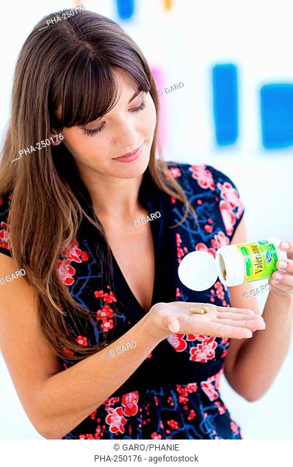 Woman taking herbal sedative capsules containing extract of the valerian plant Valeriana officinalis