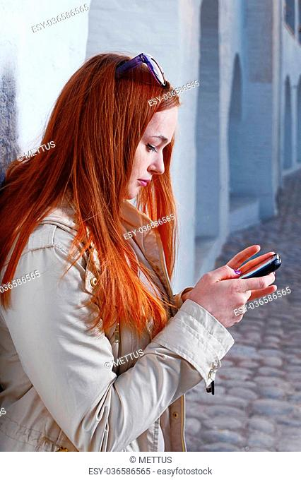 Fashionable Young Woman in Gray Coat Busy with her Mobile Phone Leaning Back Wall in a City Toned Image