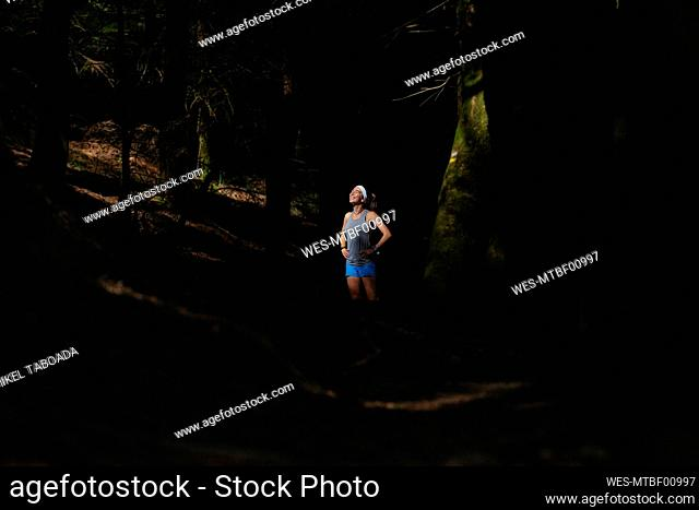 Smiling woman standing in dark forest