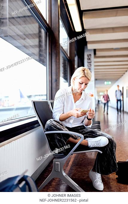 Woman using cell phone at airport