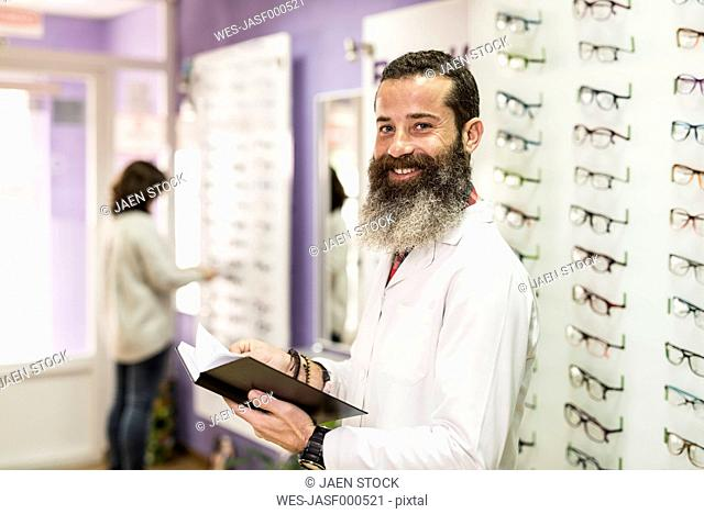 Portrait of smiling bearded optometrist in his store