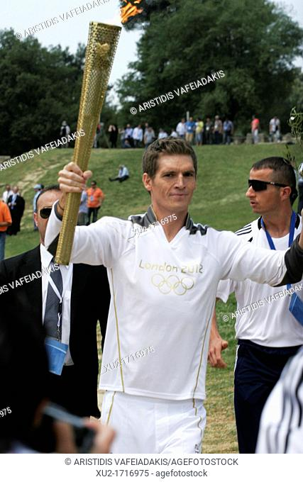10 April, 2012 Olympia Greece  SPYROS GIANNIOTIS, Greece's world champion of swimming, carries the flame during the torch lighting ceremony of the London 2012...