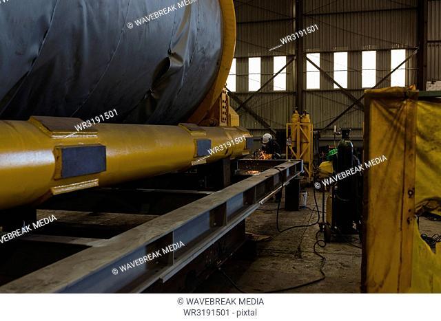 Welder repairing vessel part