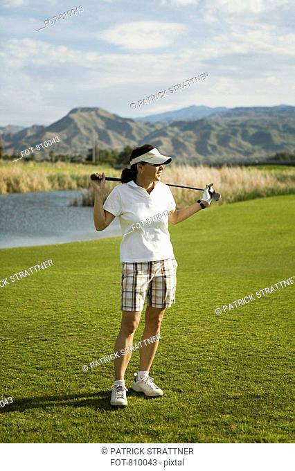 A golfer standing with golf clubs across her shoulders, Palm Springs, California, USA