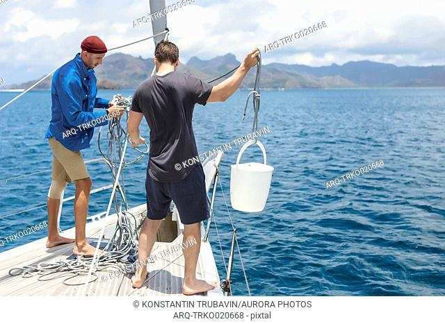 Full length shot of two men with bucket on sailboat