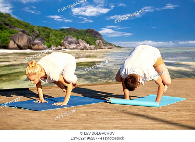 fitness, sport, yoga and people concept - couple making side crow pose on mat over exotic tropical beach background
