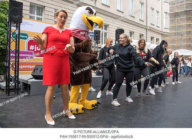 """17 August 2019, Berlin: Franziska Giffey (SPD, l), Federal Minister for Family Affairs, dances with the mascot of the """"""""Children's Ministry"""""""" and the members of..."""