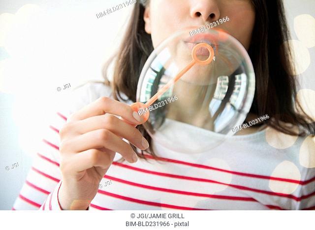 Hispanic woman blowing bubbles