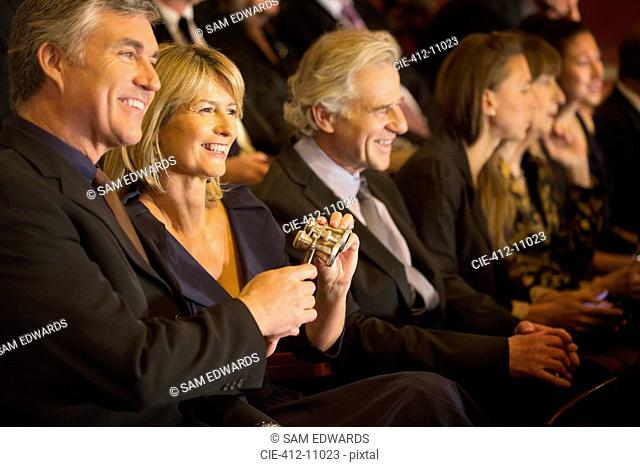 Smiling couple holding opera glasses in theater audience
