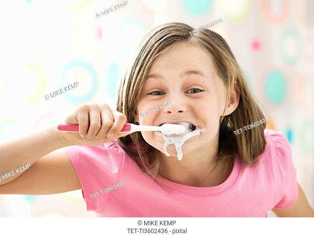 USA, Utah, Lehi, girl 10-11 brushing teeth in messy way