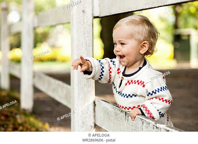 Baby girl pointing away at fence in park