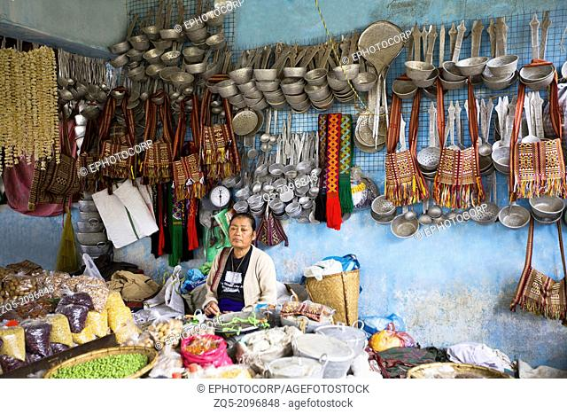 Lady selling vegetables and utensils. Bomdila bazaar, Arunachal Pradesh, India