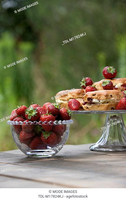 Strawberries in a glass bowl, scones with cream and jam on a cake stand
