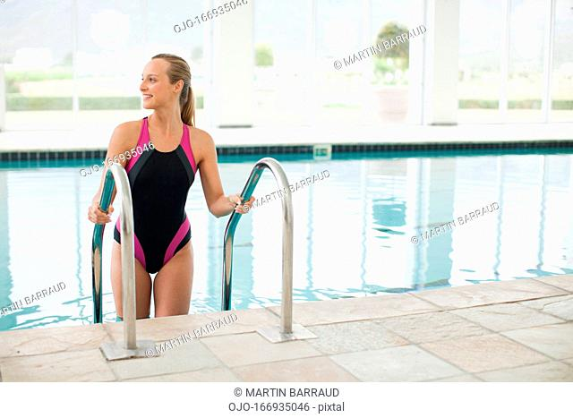 Portrait of smiling woman on ladder in swimming pool