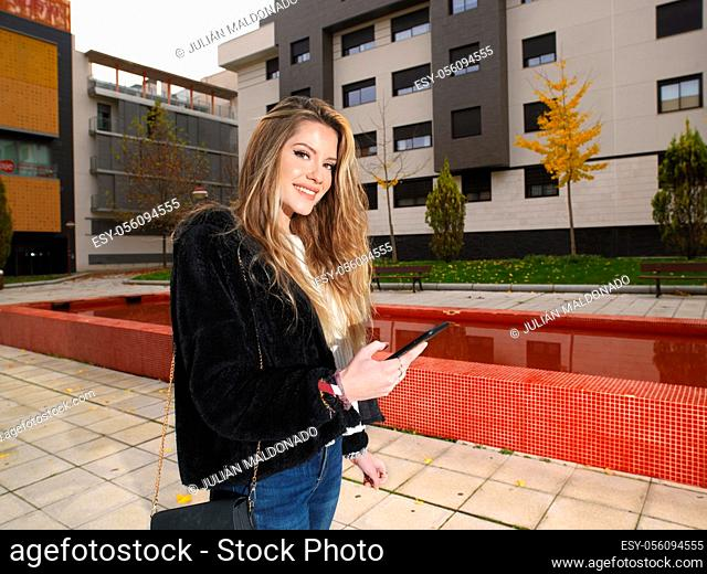 Young woman checking messages on her mobile phone