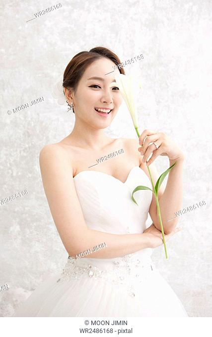 Smiling bride holding a lily
