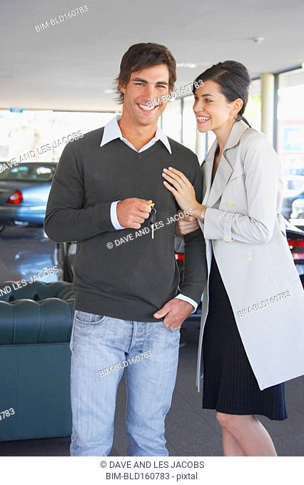 Caucasian couple buying sports car in dealership