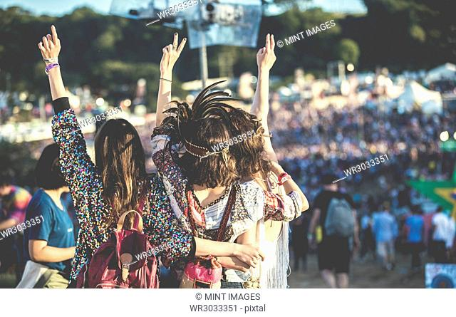 Rear view of three young women standing side by side at a summer music festival wearing feather headdress, arms raised