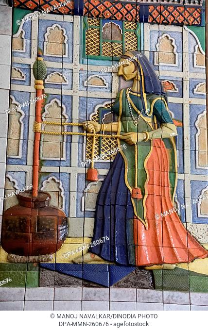 Lady churning butter milk on ceramic tiles at Chail Palace, Himachal Pradesh, India, Asia