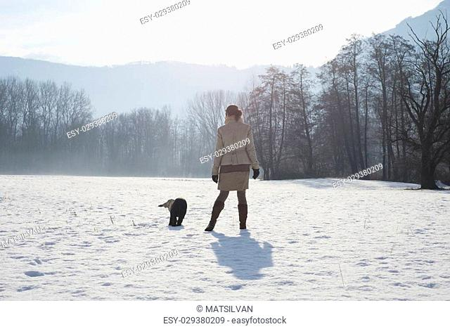 Woman walking with her dog in the snow
