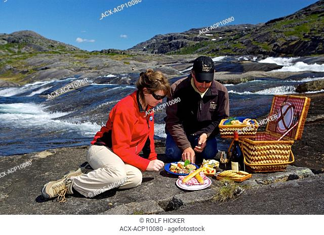 A couple enjoying a picnic beside a waterfall with a Helicopter in the background in the Mealy Mountains, Southern Labrador, Newfoundland & Labrador, Canada