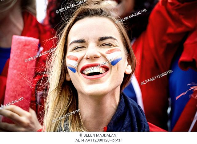 French football fan smiling at match, portrait