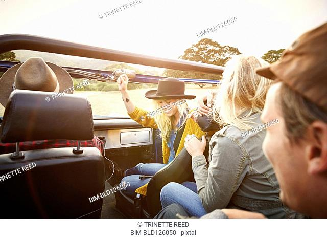 Friends driving in truck in rural landscape