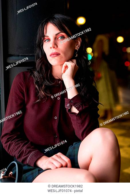 Portrait of a young woman in the city at night