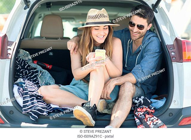 Couple in car boot looking at smartphone