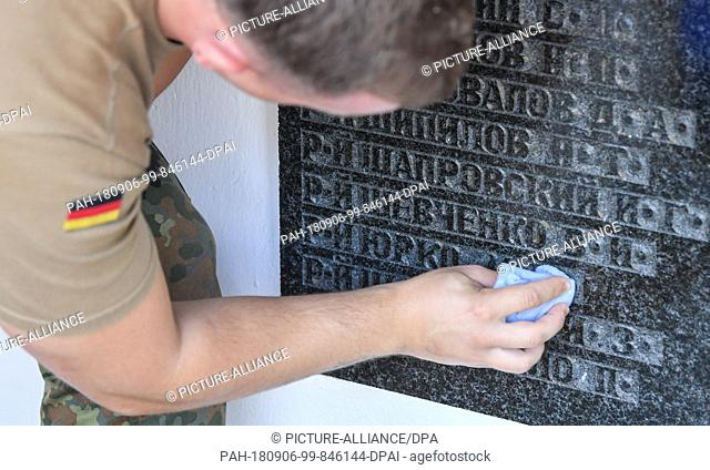 06.09.2018, Brandenburg, Lebus: A German soldier cleans a memorial plaque with the names of Red Army soldiers killed in the Second World War on the Soviet war...