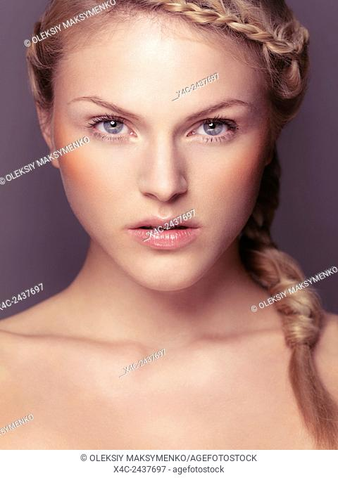 Beauty portrait of young woman face with blond braided hair and grey eyes