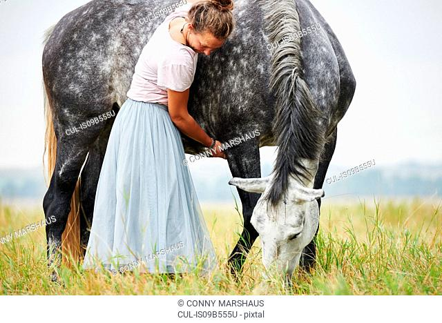 Woman in skirt with arms around dapple grey horse in field