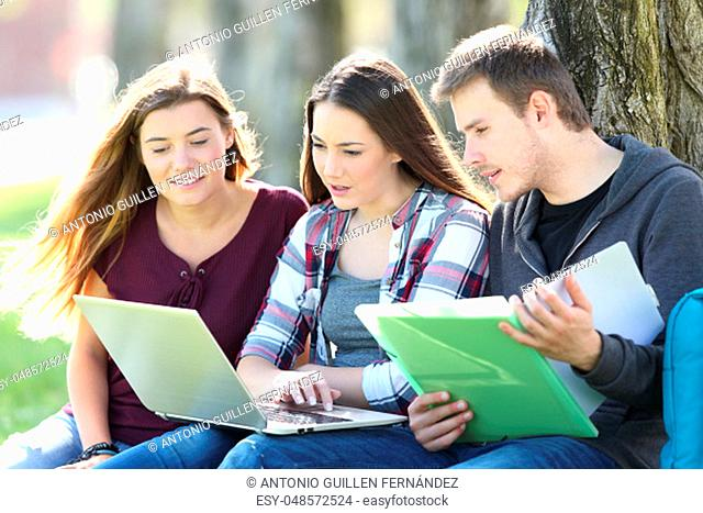 Three attentive students learning on line together with a laptop and notebook sitting on the grass in a park