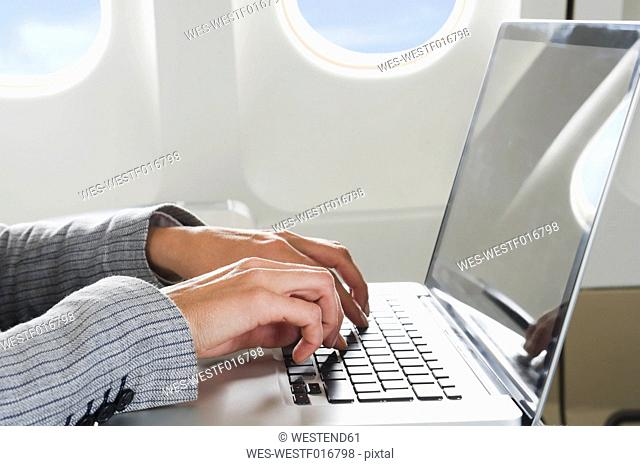 Germany, Bavaria, Munich, Close up of businesswoman's hand using laptop in business class airplane cabin