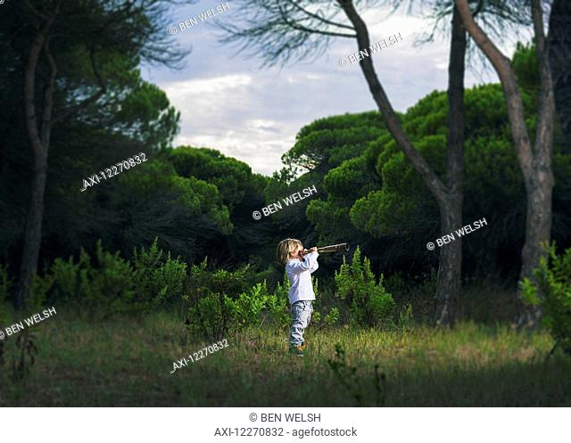 A young boy looks through a telescope standing in the grass; Tarifa, Cadiz, Andalusia, Spain